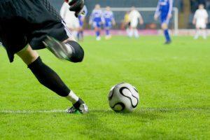 Player kicking ball on irrigated pitch